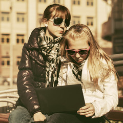 School girls using laptop on the bench