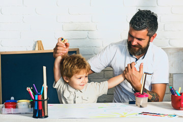 Happy family. The boy and his father are playing in the children room. Funny homework to prepare for school. Preschooler and his father enjoy the day. Bearded father and cute son
