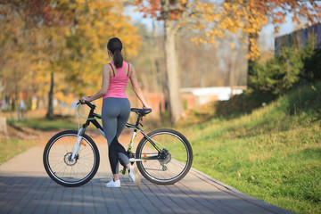 Young beautiful girl in sportswear stands next to a bicycle on the street in the park in autumn.