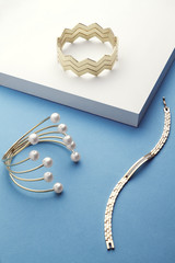 Golden bracelet collection on white and blue background