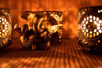 Golden ganesha figure with candle light on a wooden mat.