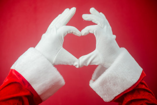Santa claus showing love heart shape sign for Christmas and Valentines day holidays decoration background. Closeup of seasonal happiness and amazing time.