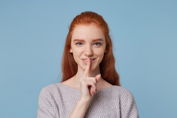 Headshot of attractive cheerful red-haired young female depicts a gesture of silence,keeps finger at her mouth,playfully looks at the camera, smiles,asks to keep a secret,privacy,over blue background.
