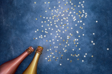 Two champagne bottles with golden confetti on blue background. Copy space, top view, flat lay