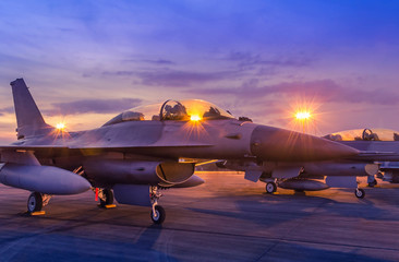 Silhouette fighter jet military aircrafts parked on runway in twilight time with light airport during air flight show in the night