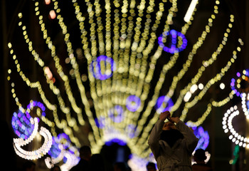 A woman takes photographs of Christmas lights in the centre of Valletta