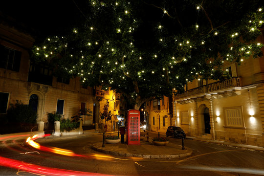 Decorative Christmas lights are seen in a tree over a telephone booth in Sliema
