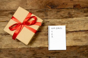 2019 Goals on blank paper notebook with Gift box on wood table for New Year Resolution concept
