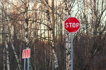 Stop sign and detour on the side of an asphalt road