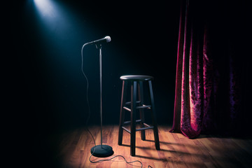 microphone and wooden stool on a stand up comedy stage with reflectors ray, high contrast image