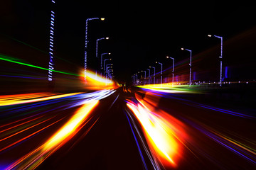 Car moving on highway against dark night, photograph is taken with long exposure.