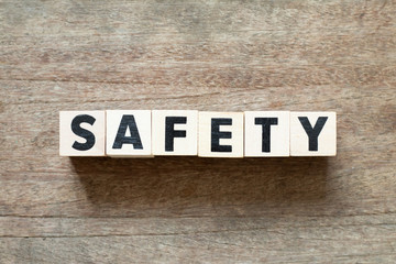 Letter block in word safety on wood background