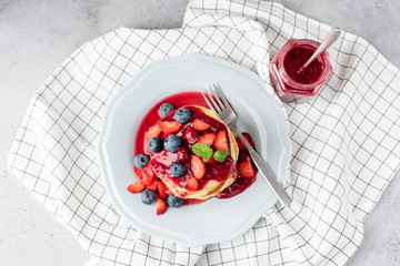 Pancakes with berries and berry sauce blueberry strawberry cranberry, table top view on white textile
