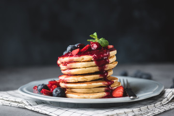 Pancakes with berry sauce and berries over dark background. Pancakes stack with blueberries, strawberries and sweet sauce. Closeup view