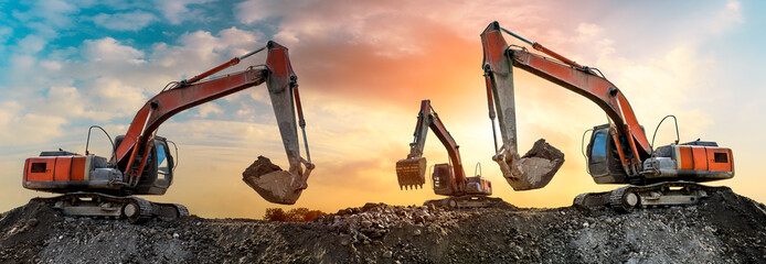 Three excavators work on construction site at sunset,panoramic view Wall mural