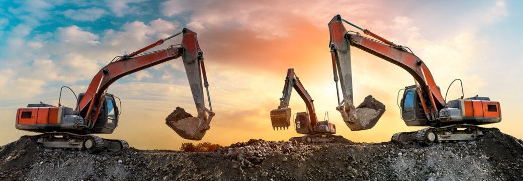 Three excavators work on construction site at sunset,panoramic view