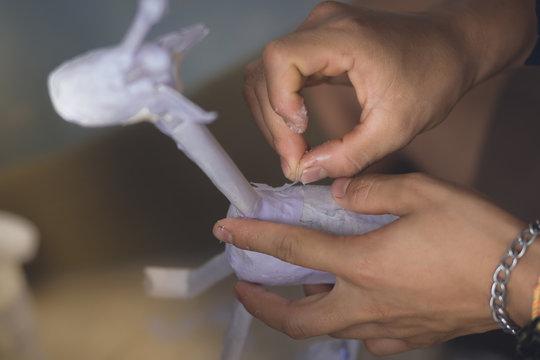 Students learn to make paper mache art as a giraffe in school.