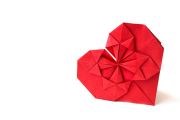 Isolated red paper heart made in origami technique on a white background. Concept of love, celebration, care, health, life