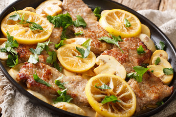 Scaloppini veal cooked with mushrooms and lemons in a spicy sauce close-up in a frying pan. Horizontal