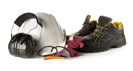 Work safety and protection equipment - protective shoes, safety glasses, gloves and hearing protection over white