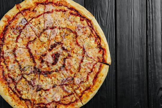 pizza barbecue sauce with chicken on black wooden background top view