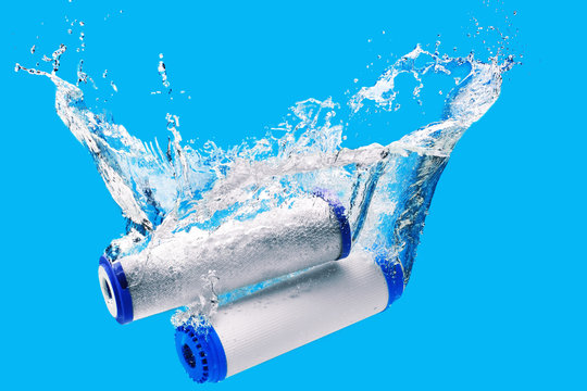New carbon filter cartridge for house water filtration system isolated on blue background. Splash. Concept.