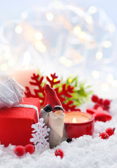 Christmas composition with a candle, gifts and festive decorations оn the snow. Christmas or New Year greeting card.