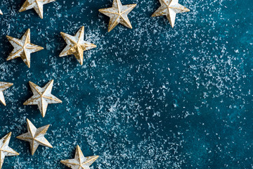 White golden stars on snowy dark blue background. Christmas New Year greeting card poster banner. Vintage retro style. Creative image. Magic atmosphere