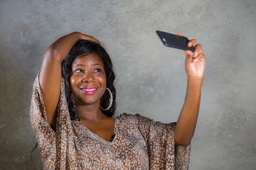 young beautiful and happy black afro American woman smiling cheerful taking selfie portrait photo with mobile phone camera for using on internet social media isolated