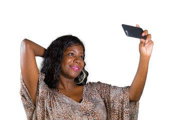 young beautiful and happy black African American woman smiling cheerful taking selfie portrait photo with mobile phone camera for using on internet social media isolated