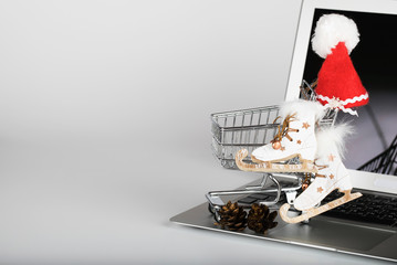 Mini shopping cart with Santa Claus hat and wooden decorative ice skates.