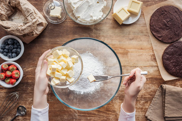 partial top view of woman mixing ingredients and preparing dough for homemade cake