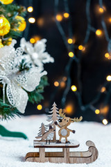 Wooden sleigh with deer and Christmas tree on snow on bokeh background garland