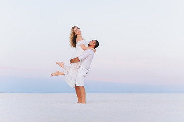 A bearded man takes on his hands a blond woman on a background of white sand and bright sky. Portrait of emotional people at sunset. Love in the desert newlyweds. The love story of merry and lovers.