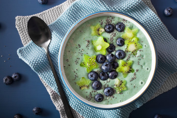 healthy spirulina smoothie bowl with blueberry, kiwi stars, chia seed