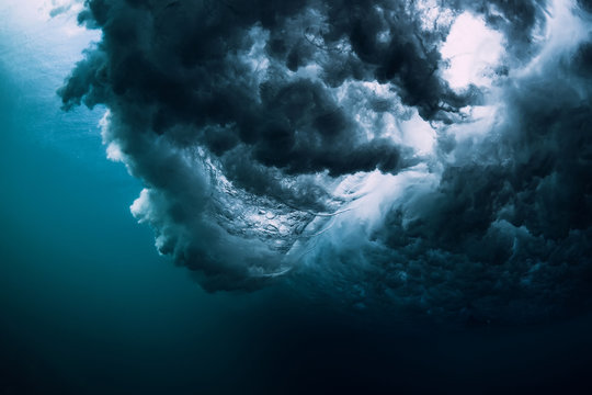 Blue powerful wave crashing in ocean. Underwater wave with foam and air bubbles.