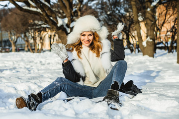 Young smiling woman in winter coat having fun outdoor