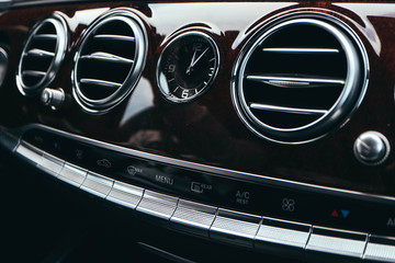 Luxury car dashboard, air conditioner, clock, buttons.