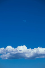 Moon on a clear blue sky, fluffy clouds, calm beautiful view.