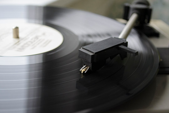 old player with vinyl record on black background