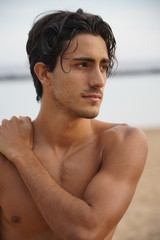 Handsome male touching shoulder and looking at camera on beach