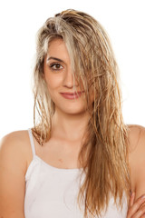 smiling blond woman with wet hair on white background