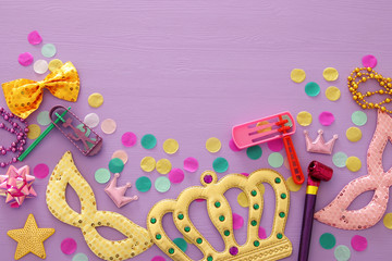 Purim celebration concept (jewish carnival holiday) over purple, pink wooden background. Top view.