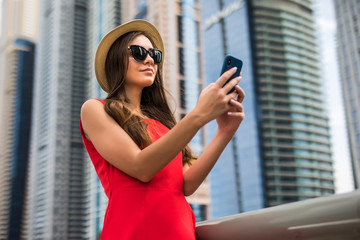 Portrait of young smile woman in red dress, sunglasses and summer hat typing message or scroll screen of phone on downtown skycrapers background