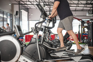 elderly Man at the gym exercising on the xtrainer machines - Image