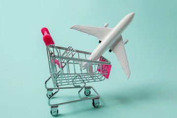 Miniature toy model plane, supermarket grocery push cart for shopping on blue pastel colorful paper trendy background. Sale travel by plane weekend sea adventure trip journey buy ticket tour concept