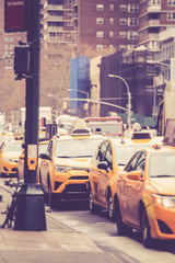 Vintage toned image of Line of New York City yellow taxicabs on street in Manhattan