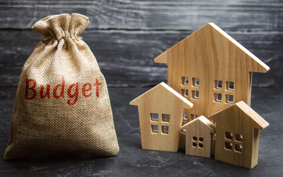 Bag with money and the inscription Budget and wooden houses. The concept of the city budget. Financing in the country. Investing money in real estate. Budgeting. Saving and accumulation of money