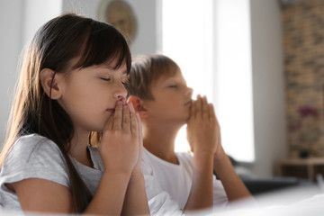 Cute children praying near bed at home