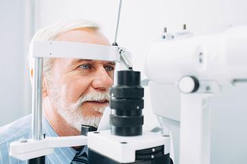 Senior patient receiving eye exam at clinic, eyesight examination aged people